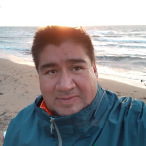 Selfie of Clifford Paul wearing a blue jacket,behind him you can see the sea andn the beach, and how the sun is shining.